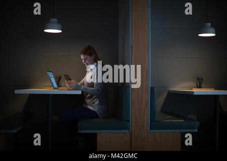 Businesswoman working late at night in office alone - Stock Photo