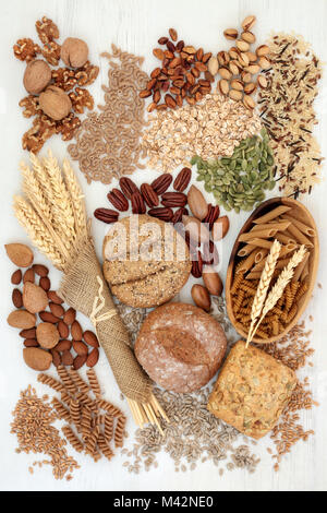 Food with high fibre content with whole grain bread rolls, whole wheat pasta, grains, nuts, seeds and cereals. - Stock Photo