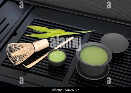 Japanese green matcha tea with powder and health drink in cup with whisk and stick stirrer with bamboo leaf on black - Stock Photo