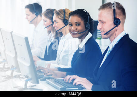 Male and female customer service representatives working at desk seen through glass - Stock Photo