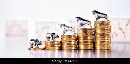 Stack of coins with Bull and Bear and graphics with market prices in the background - Stock Photo