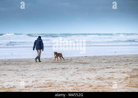 A man walking his pet Boxer dog along the shoreline on a windy Perranporth Beach in Cornwall UK. - Stock Photo
