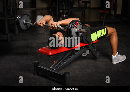 Young man doing arms bench french press workout in gym - Stock Photo
