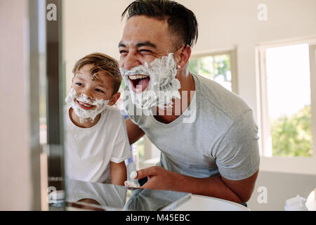 Happy father and son having fun while shaving in bathroom. Young man and little boy with shaving foam on their faces - Stock Photo