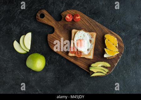top view of toast with fried egg and cherry tomatoes for breakfast on cutting board - Stock Photo