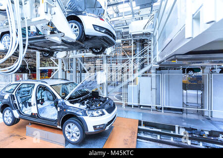 Assembling cars on conveyor line - Stock Photo