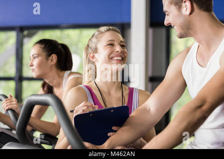 Trainer woman talking with a man doing exercise bike - Stock Photo