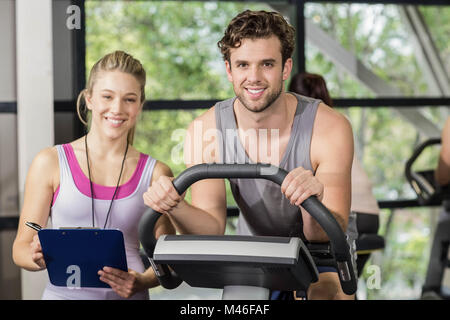 Trainer woman with a man doing exercise bike - Stock Photo