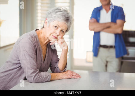 Portrait of worried senior woman with man standing in background - Stock Photo