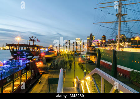 Hamburg, Germany - January 27, 2014: Quay at the landing bridge at the evening with harbour ferry and leaving crowd - Stock Photo