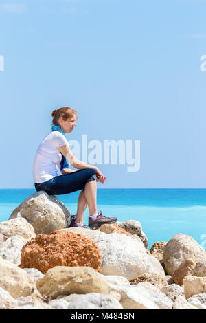 Caucasian woman sitting on rocks at coast near sea - Stock Photo