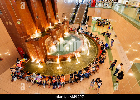 Singapore Ngee Ann City Shopping Mall. Shoppers likes to gather and sit around the water fountain in the basement - Stock Photo