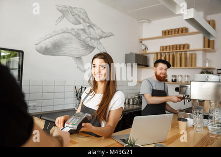 Coffee Business Concept - Beautiful female barista giving payment service for customer with credit card and smiling - Stock Photo