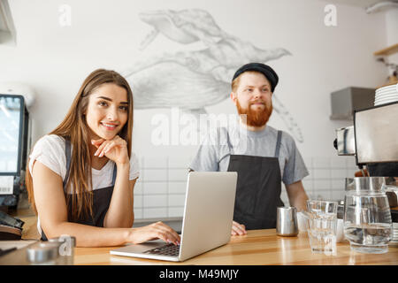 Coffee Business Concept - Cheerful baristas looking at their laptop for online orders in modern coffee shop. - Stock Photo