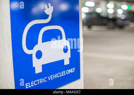 Sign For Electric Car Charging Point In Car Park - Stock Photo