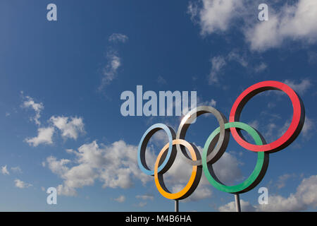 LONDON, UK - February 15th 2018: The Olympic symbol, made up of five interconnected coloured rings, under a blue - Stock Photo
