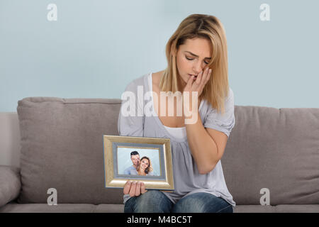 Sad Woman Holding Broken Picture Frame Of Couple In Love - Stock Photo