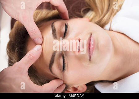 Close-up Of A Therapist Massaging A Beautiful Woman's Forehead At Beauty Spa - Stock Photo