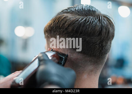 Getting perfect shape. Close-up side view of young bearded man getting beard haircut by hairdresser at barbershop. - Stock Photo