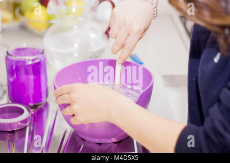 female hands in flour kneading dough on table - Stock Photo