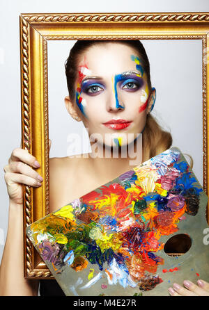 Young woman painter in golden frame with color pallet - Stock Photo