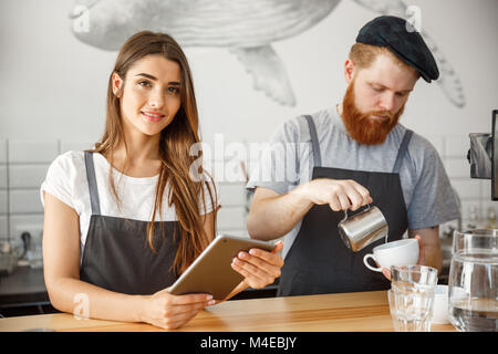 Coffee Business Concept - Cheerful baristas looking at their tablets for online orders in modern coffee shop. - Stock Photo