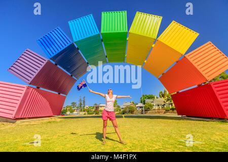 Fremantle, Australia - Jan 7, 2018: Australia travel welcome. Happy woman with Australian flag enjoys rainbow sea - Stock Photo
