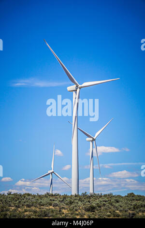 wind turbines generating electricity on a windy sunny day - Stock Photo