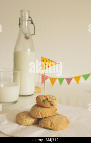 A pile of handmade cookies for children with a bottle and glass of milk in the background and happy, cheerful decoration. - Stock Photo