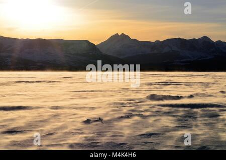 Snow blows across a frozen lake at sunset, with majestic snow covered mountains in the distance - Stock Photo