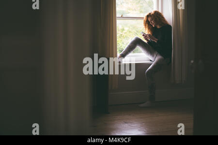 Woman using mobile phone while sitting on windowsill - Stock Photo
