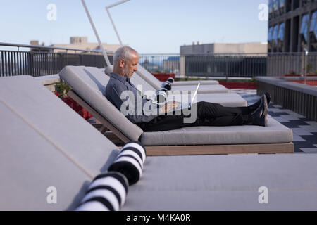 Businessman using a laptop while resting on a sun lounger - Stock Photo