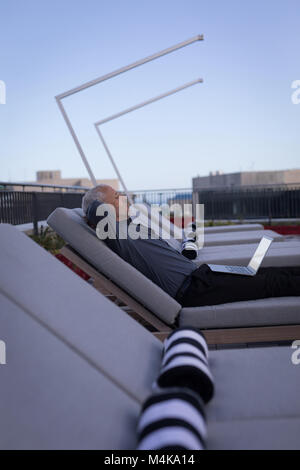 Businessman resting on a sun lounger - Stock Photo