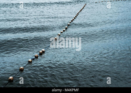 Line of white saferty buoy on seascape. - Stock Photo