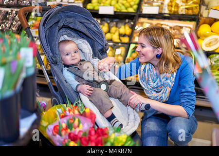 Young woman with baby son in grocery store - Stock Photo