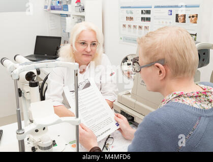 SAINT PETERSBURG, RUSSIA - FEBRUARY 13, 2018: Optometrist doctor chooses reading glasses for Mature woman. Doctor - Stock Photo