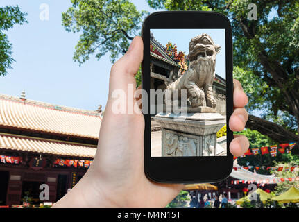 travel concept - tourist photographs outdoor lion statue in Guangxiao Buddhist Temple (Bright Obedience, Bright - Stock Photo
