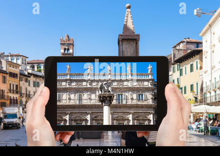 travel concept - tourist photographs square Piazza delle Erbe in Verona city in Italy on tablet - Stock Photo