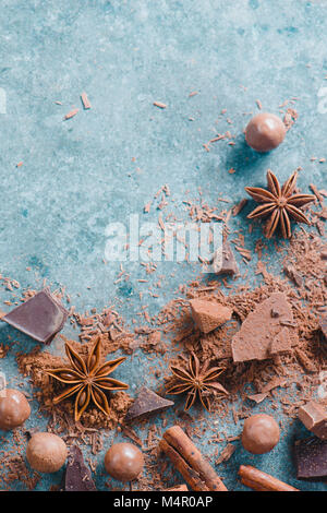 Dessert ingredients flat lay. Chunks of milk and bitter chocolate, spices and scattered cocoa on a stone background. - Stock Photo