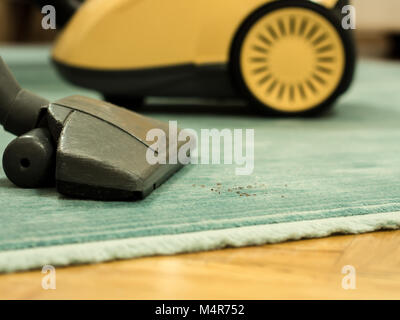 vacuuming the carpet at home with vacuum cleaner - Stock Photo