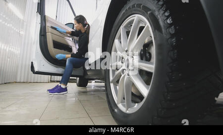 Young woman in blue gloves is cleaning interior of the car for luxury SUV - Stock Photo