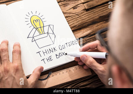 Businessman Drawing The Think Outside The Box Concept Chart On Notebook With Black Marker - Stock Photo
