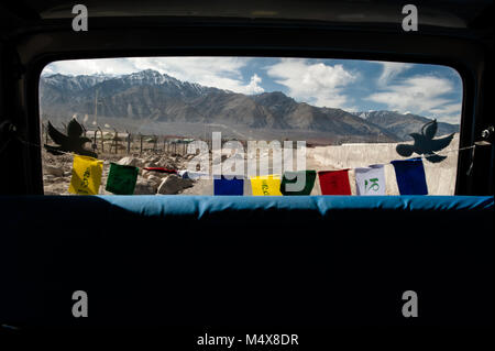 Buddhist prayer flags hang in the rear window of a vehicle in Leh, Ladakh. - Stock Photo
