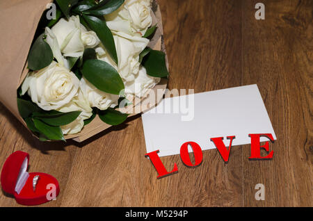 inscription love on a wooden background with a white sheet of paper and a bouquet of white roses in kraft paper - Stock Photo