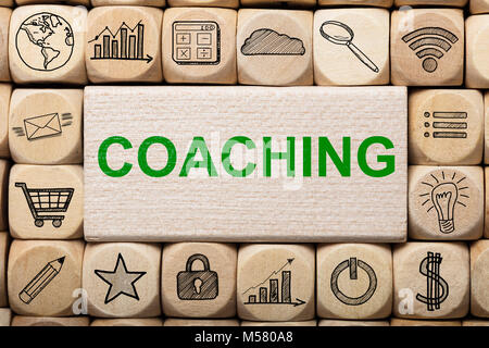 Full frame shot of coaching text on wooden block surrounded by various computer icons - Stock Photo
