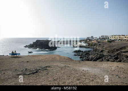 View of the small habour of village El Cotillo, Fuerteventura, Canary Islands, Spain. A small boat leaving the habour, - Stock Photo