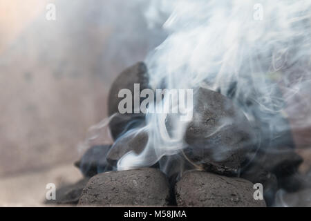 Fire up the grill with briquettes with a lot of smoke - Stock Photo