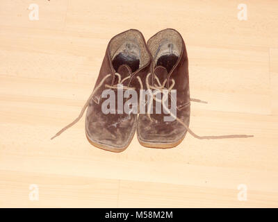 close up brown dirty muddy walking shoes wooden floor; essex; england; uk - Stock Photo