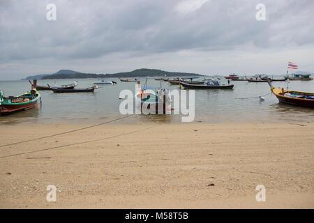 row of Thai fishing boats lined up at Rawai Beach - Stock Photo