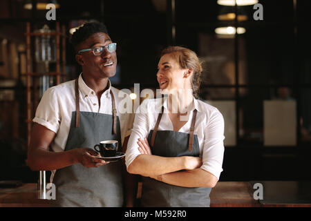 Happy coffee shop owner couple standing inside their shop. Man and woman baristas standing inside their café wearing - Stock Photo